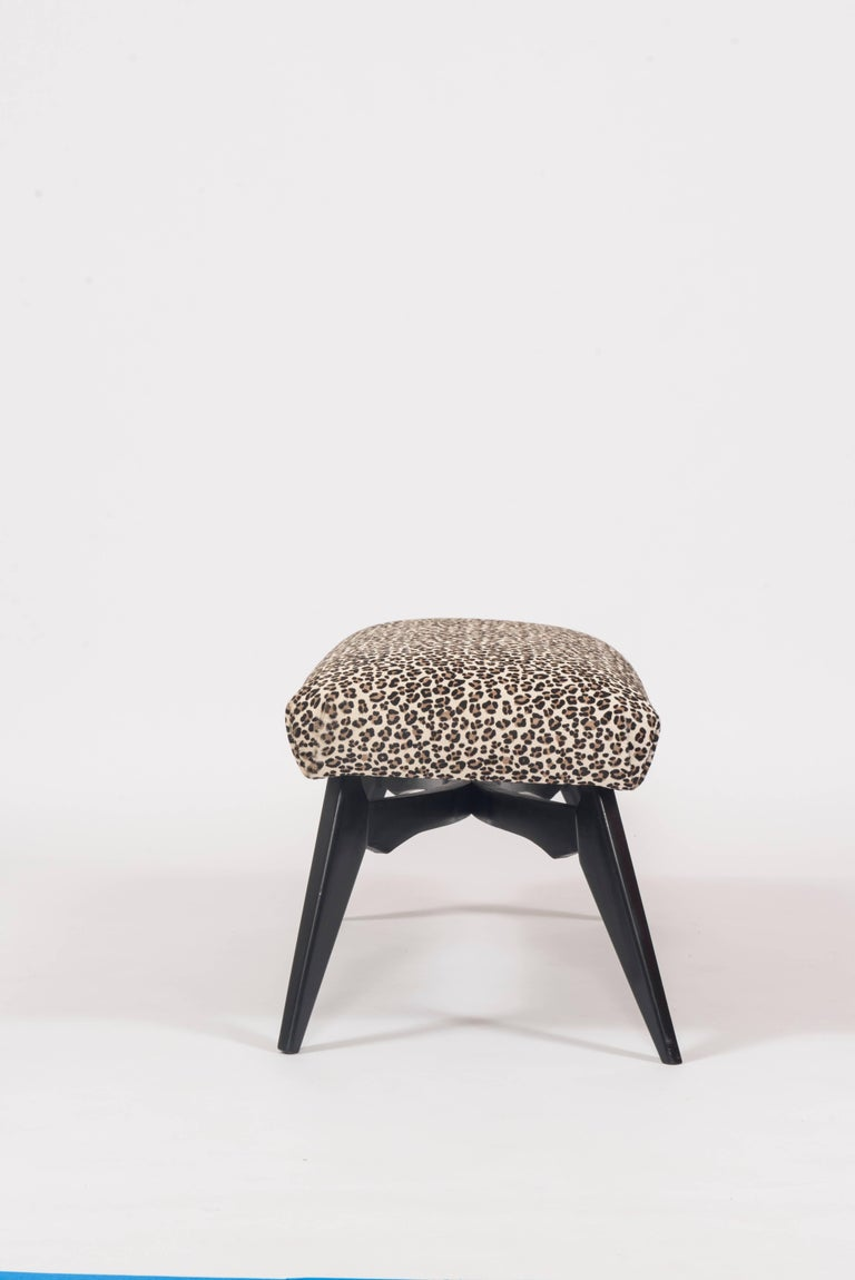 Italian Mid-Century Modern ebonized bench with splayed legs, newly upholstered in a leopard print hair hide, circa 1960, Milan.