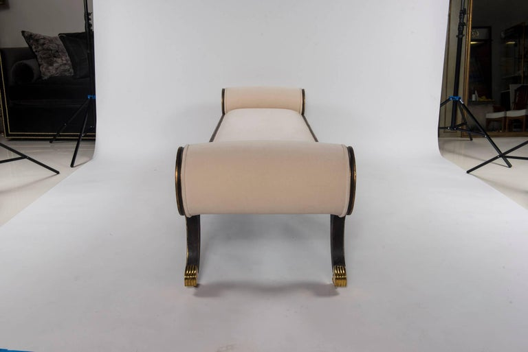 A painted and giltwood Federal style banquette with brass feet and casters newly upholstered in a low pile ecru velvet.  This banquette is also available C.O.M. and in several custom lengths 72 inches $7800.00, and 92 inches $8600.00.