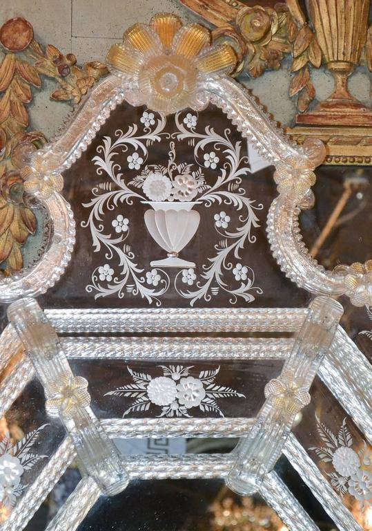 Marvelous antique Venetian mirror with etched glass in floral and urn motif. Having wonderful glass trimmed octagonal frame and beautifully adorned with parcel-gilt rosettes and flowers.