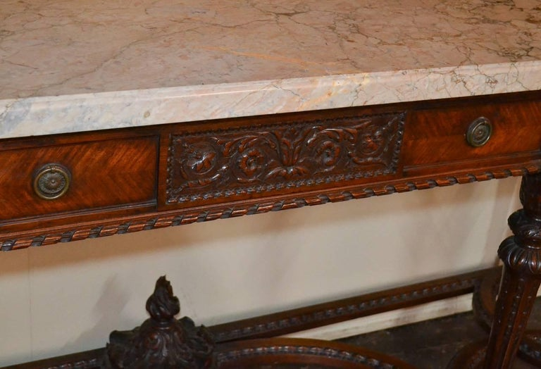Beautiful French Louis XVI three-drawer console. Having wonderful carved walnut detailing, thick Rose de Brignoles marble top, and lovely designed stretcher. A great quality piece that would suit many types of decor!