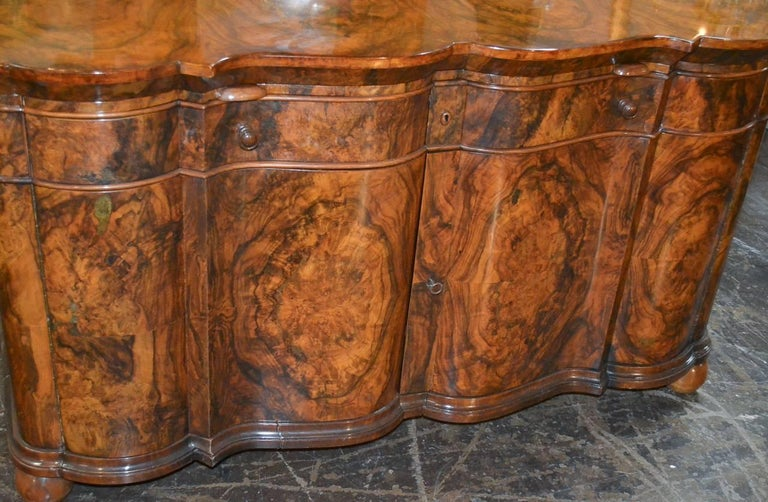 Great quality Italian burl walnut two-drawer over two-door buffet. Having impressive shaped front, stunning finish and patina, and resting on ball feet. Fabulous for numerous designs!
