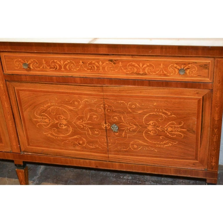 Fine quality early 20th century Italian mahogany credenza or sideboard with a white marble top. Fitted with two long drawers and two large cupboards. Exquisite satinwood marquetry inlays overall of stylized vines, leaves, and fleur de lis. The