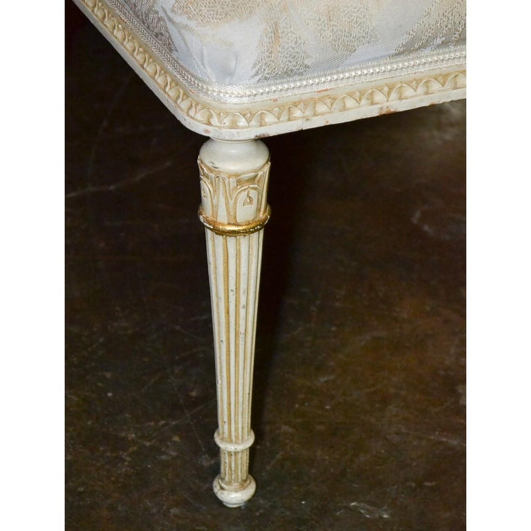 Elegant 19th century French Louis XVI style parcel-gilt and painted bench with upholstered top. Hard-carved and raise on tapered and fluted legs,