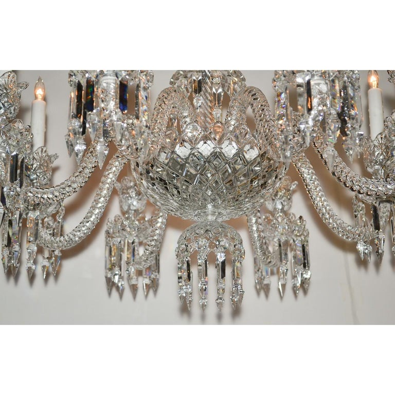 Exquisite signed Baccarat cut crystal chandelier of paragon quality. The scalloped and vase-shaped crown atop curved projections with flower-cup dangles and icicle prisms. The diamond patterned contoured stem mounted with eight gracefully scrolled