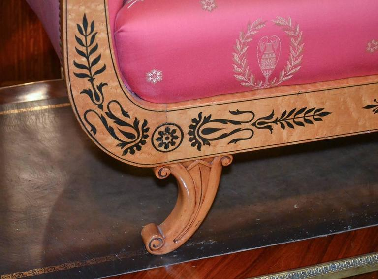 Fantastic Austrian Biedermeier maple settee, circa 1880. Having lovely ebony foliate inlays against a warm beautiful finish. Upholstered in vibrant red fabric with wreath and urn motif, and having gracefully curved lines.