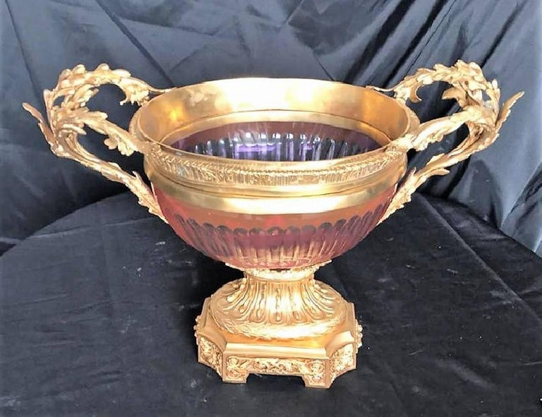 Exquisite vintage French gold-gilded bronze and cranberry colored glass centrepiece with ornate leaf scroll handles. The fluted bowl encased in doré bronze with stylized rim.