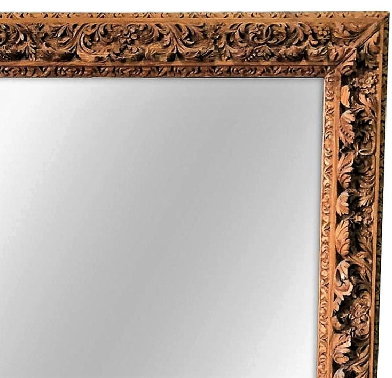 Remarkably carved 19th century, French pine wall mirror. The ornate frame with intricately carved leaf scrolls, flowers and vines.