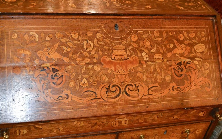 Marvelous 19th century Continental oak bureau with marquetry inlays. Having detailed and intricate inlays in floral and acanthus leaf motif, brass hardware, and lovely fitted interior. A charming piece for any design!