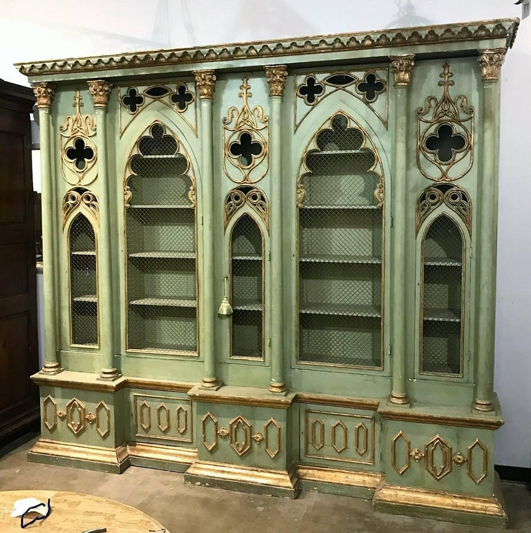 Particularly Fine late 19th century Italian Gothic Revival breakfront cabinet bookcase with parcel-gilt accents. The molded out-swept leaf carved cornice above Gothic arched shaped grilled doors with trefoil carvings divided and flanked by pilasters