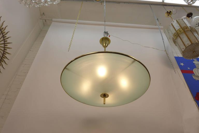 A very large pair of flying saucer chandeliers. They are made of solid brass and etched convex glass, each composed of two frosted glass domes. Made to order. Four regular sockets Max. 100 watts per socket.