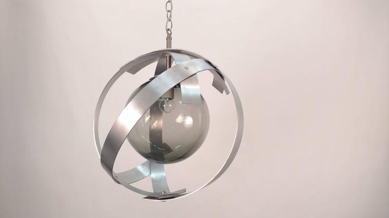 Orbit aluminium frames with smoked glass globes. Newly wired. Two different sizes: Main picture: Two side fixtures are 36in H x 16in D Middle pendant is 39in H x 18in D.
