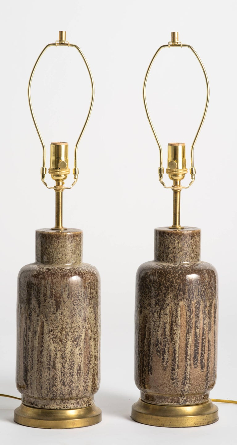 Pair of glazed table lamps in mottled brown and beige tones.