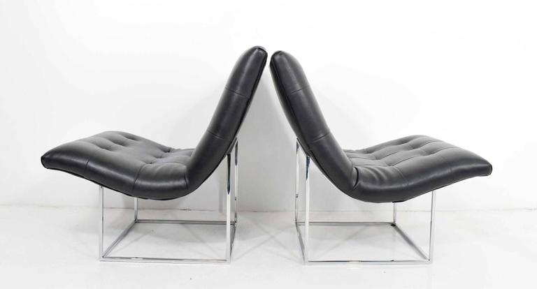 Pair of Milo Baughman lounge chairs in tufted faux leather and chrome bases.
