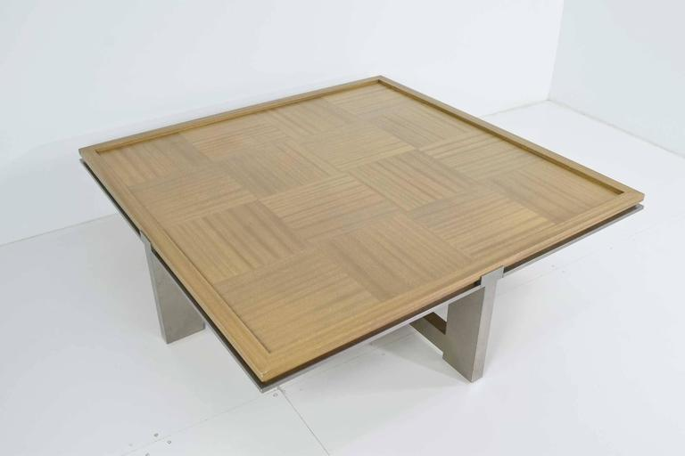 Wood is ash with a beautiful grain, down in a parquest pattern. Metal is stainless steel or other alloy in a satin finish. The table is high-quality and very well-made. It may be custom or some high-quality line.