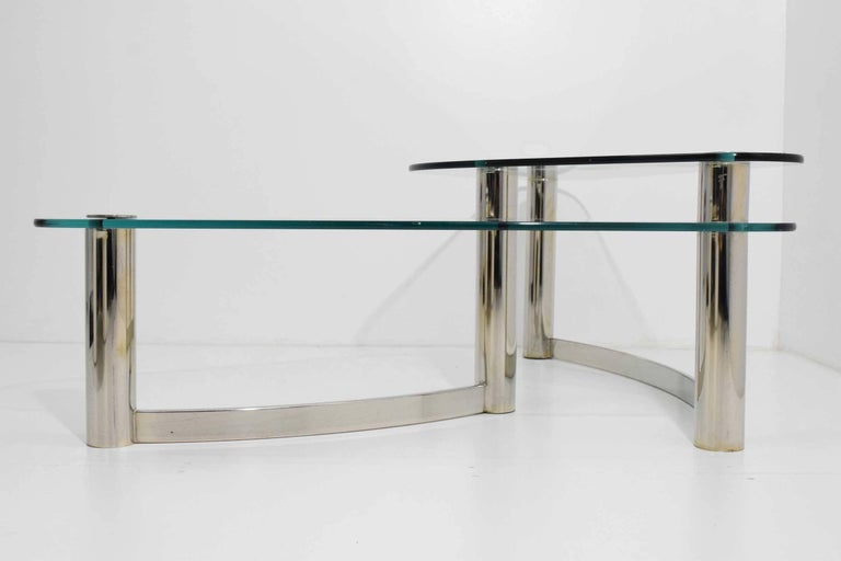 Elegant free style two-tier coffee table with polished metal base and glass tops. Very well made.