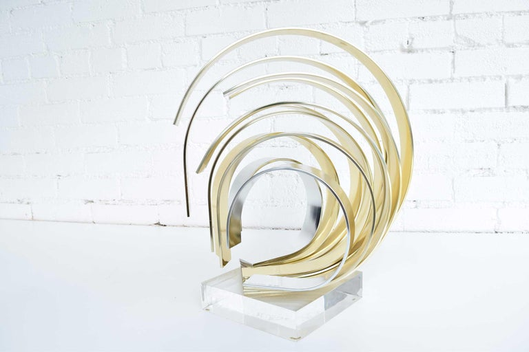 Dan Murphy signed and dated 1991. Aluminum ribbon sculpture, coated half in silver and half in gold, mounted on Lucite base. Measures: 15.5