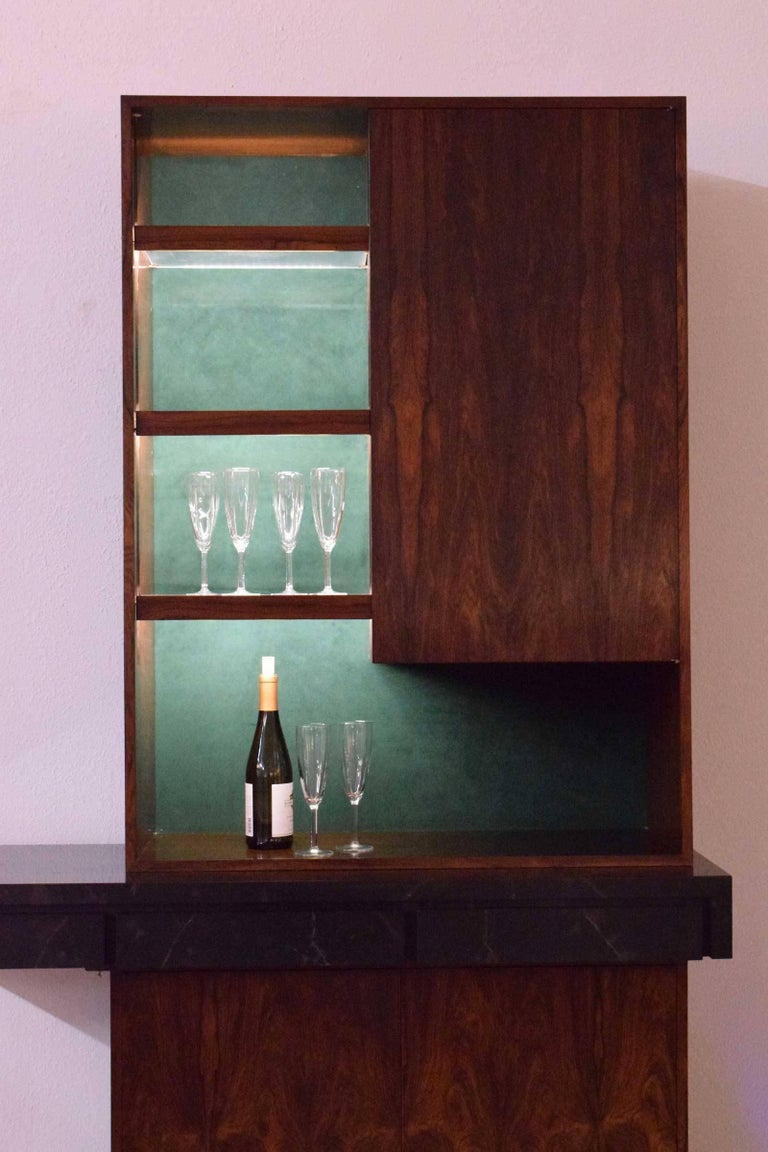 Beautiful rosewood veneer, faux marble top, felt lined drawers, lucite shelves with rosewood trim, lighting on top and bottom, wine storage.