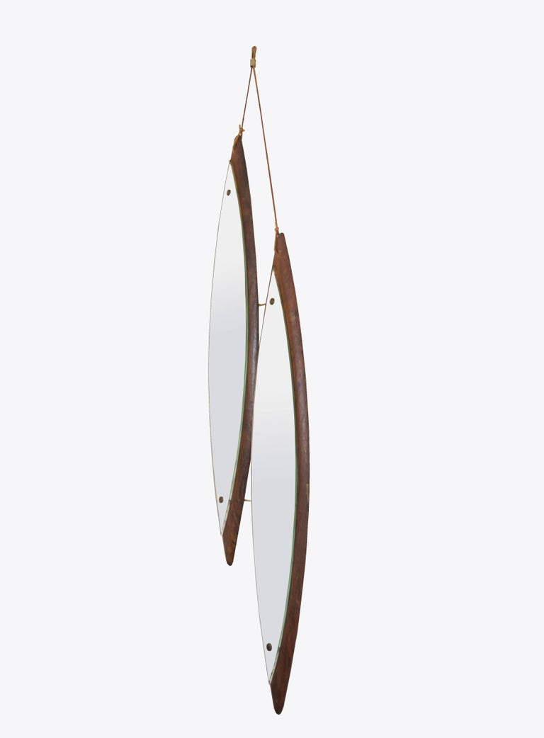 This is a highly unusual design, asymmetrical diamond shaped rosewood mirrors fastened together by brass rods and hanging by double leather straps with a brass clasp.
