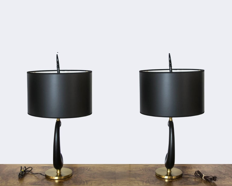 Very interesting pair of amoeba shaped black enamel and brass lamps with matching finials.
