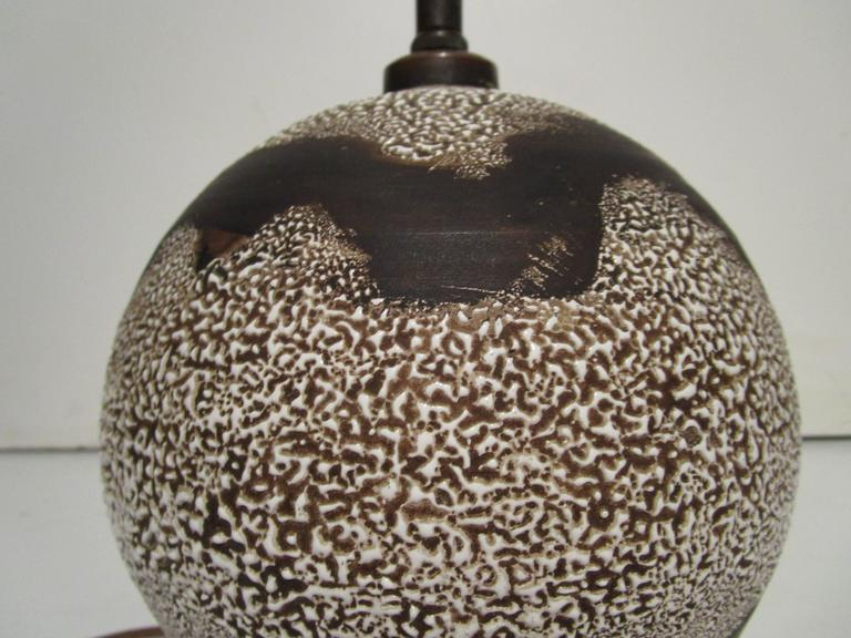 Table lamp in the style of Jean Besnard. Brown glazed spherical form stoneware with two bands of ivory textured glaze. Newly rewired with brown silk cord.  Dimensions: 8