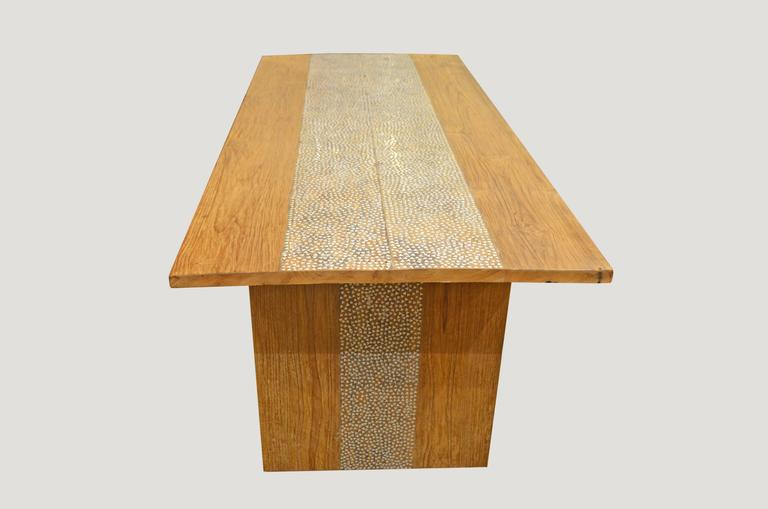 Reclaimed teak wood with added shell inlay. Perfect for inside or outside dining. Hand-cut shell inlay is inlaid into the teak wood of this minimalist style table. Can also be used as a desk or console.  Andrianna Shamaris, Inc. The Leader In Modern