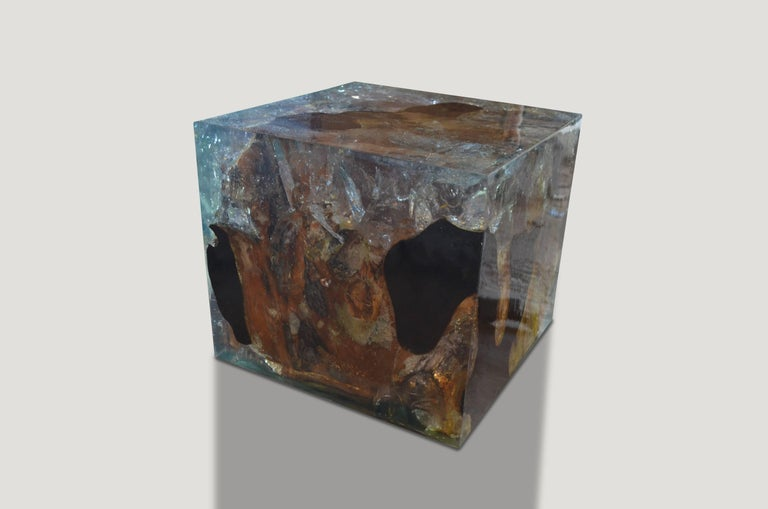 This cracked resin side table or cocktail table is made from reclaimed teak infused with aqua resin. A dramatic piece due to the depth of the resin, which resembles a unique quartz crystal with many different facets as shown here with gold, warm
