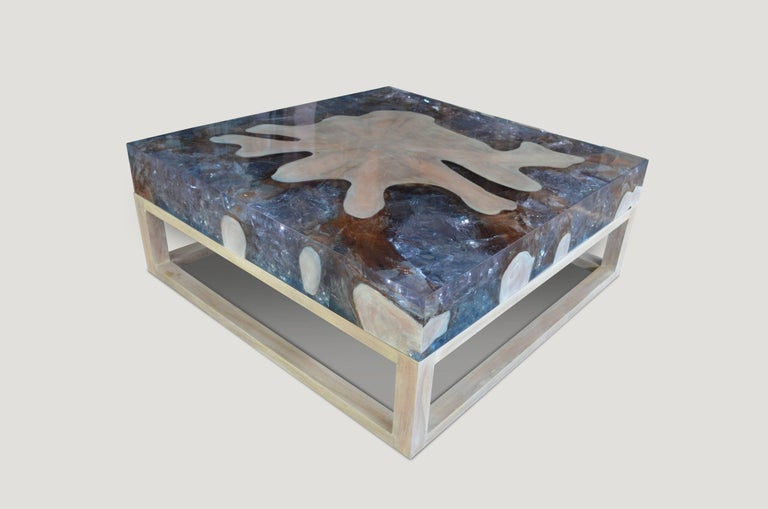 This St. Barts coffee table is made from reclaimed teak infused with aqua resin, which resembles a unique quartz crystal with many different facets, as shown here with gold, warm tones created naturally within the wood. Straight modern lines with a