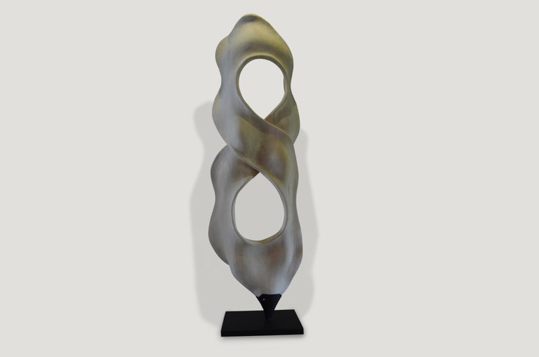Stunningly beautiful hand-carved sculpture shaped into the figure eight made from one piece of reclaimed bleached focus wood. Dramatic yet understated, this piece is set on a modern black steel stand.  The St. Barts collection features an exciting