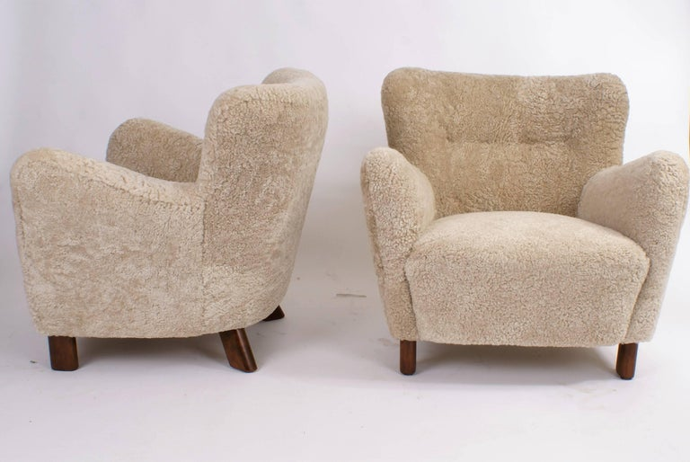 Pair of Fritz Hansen easy chairs, model 1669, circa 1930s.  Sculptural chair re-upholstered in sheepskin, legs of stained beech. All work carried out as original with filling in organic materials and bottom finish with nails.  Price is for the