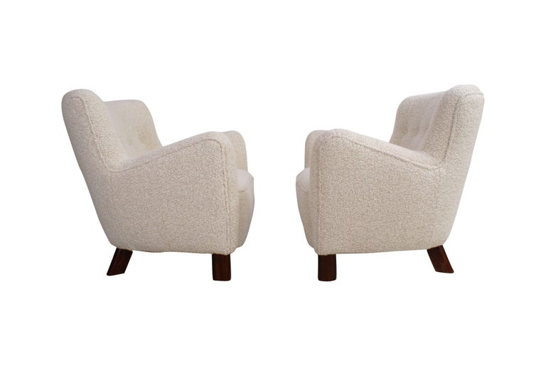 Pair of Fritz Hansen easy chairs, model 1669, circa 1930s.  Sculptural model re-upholstered in wool, legs of stained beech. All work carried out as original with filling in organic materials and bottom finish with nails.  Price is for the pair.