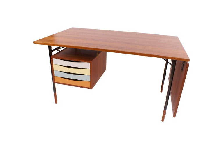 Finn Juhl freestanding teak writing desk with detachable flip-down leaf. Drawer section with four polychrome lacquered drawers. Anodized metal frame with teak shoes. Designed 1953.  Literature: