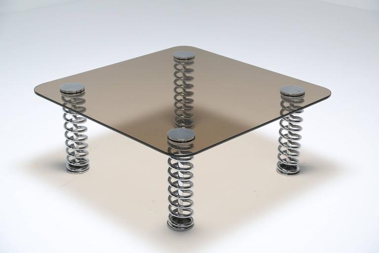 A smoked glass tabletop mounted on four rigid chrome springs. The table is very solid and does not move on the springs. This might make a good piece for a car enthusiast or in a man cave. Unknown maker but possibly British.
