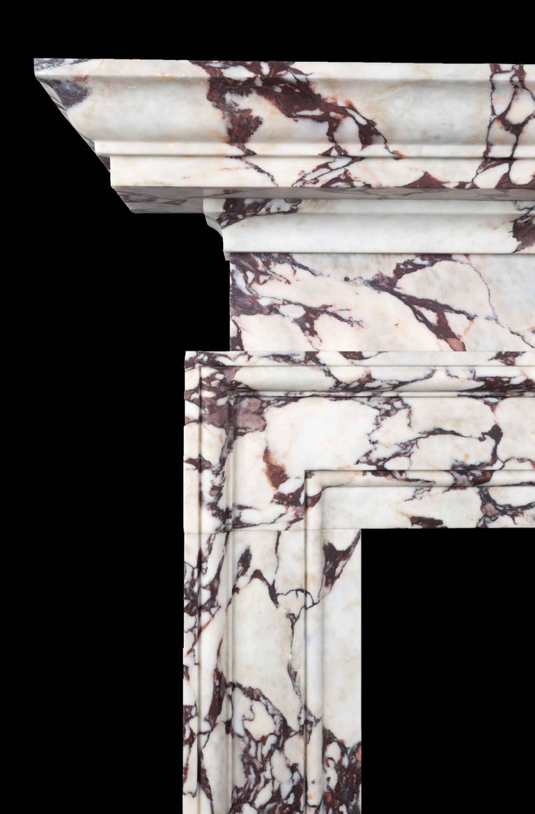 A Breccia Viola marble fireplace of stylish architectural design. The aperture surrounded by a wide frame stepped moulding. The plain and squat frieze compliments the generously sized and deep moulded cornice mantel. One of five limited edition