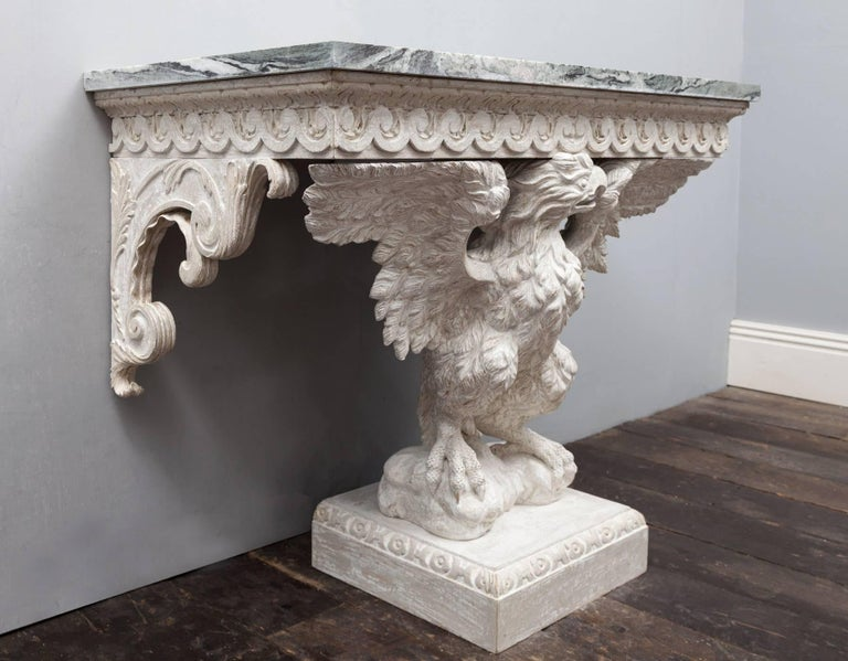 A magnificent pair of eagle console tables in the George II Palladian style. The Connemara marble tops are of the finest cut, displaying great veining and variation of colours. Each marble top is supported by a vitruvian scroll frieze, under two