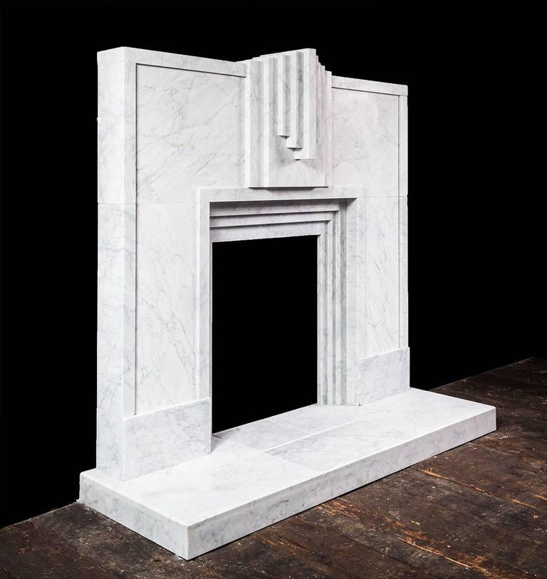 Made from beautifully veined Italian Carrara marble, the fireplace features strong, clean and bold geometric lines, all typical of the 1920s Art Deco style.