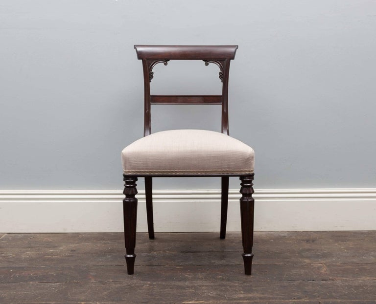 A set of ten elegant antique rosewood dining chairs. Produced during the Regency period, the chairs feature tapering turned legs, bar backs with scroll corners and neutral fabric coverings. Beautifully made from the finest rosewood, deep and rich