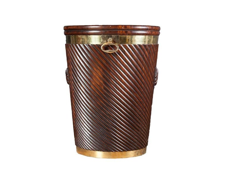 Irish turf bucket in the late Georgian style.  Large mahogany Irish turf bucket with carved scallop shell detail. The richly colored mahogany body has been polished dark and slightly distressed to simulate age. The hand-carved bucket is brass