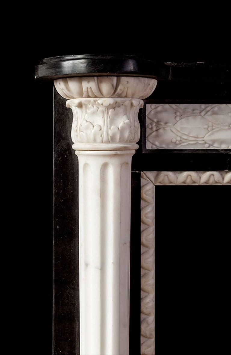 Antique French Empire style marble mantelpiece from the First Empire period.  Petit in size and made from Belgian black marble with white Italian Carrara marble elements. The fluted columns have acanthus capitals under egg and dart mouldings. The
