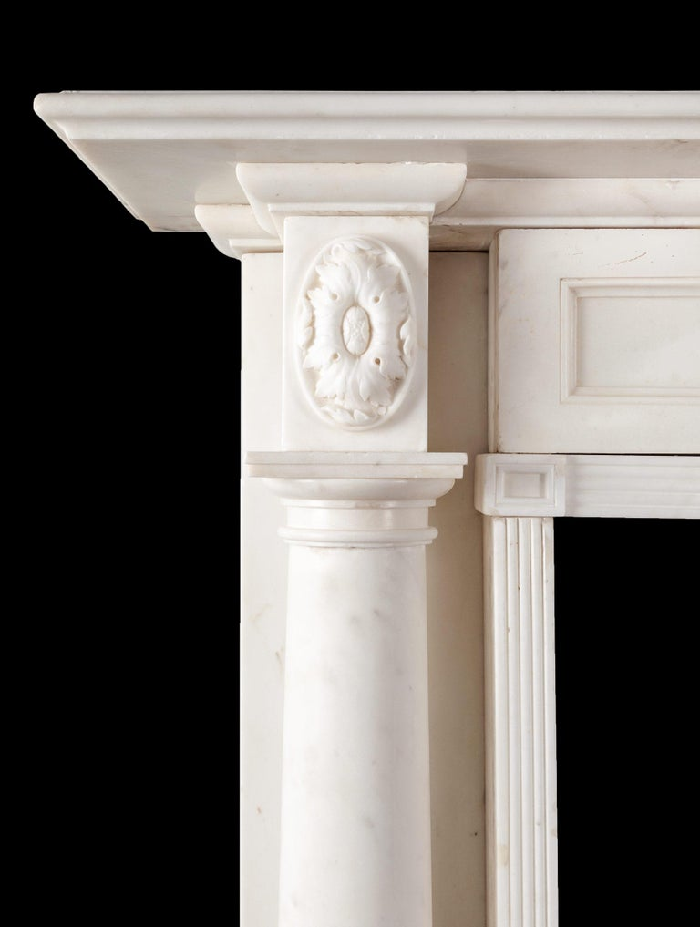 An antique statuary marble fireplace from the English Regency period. The jambs with full rounded Tuscan columns, under carved oval floral end-blocks. The opening is framed with reeded mouldings and on the lintel rests a triple panelled frieze.