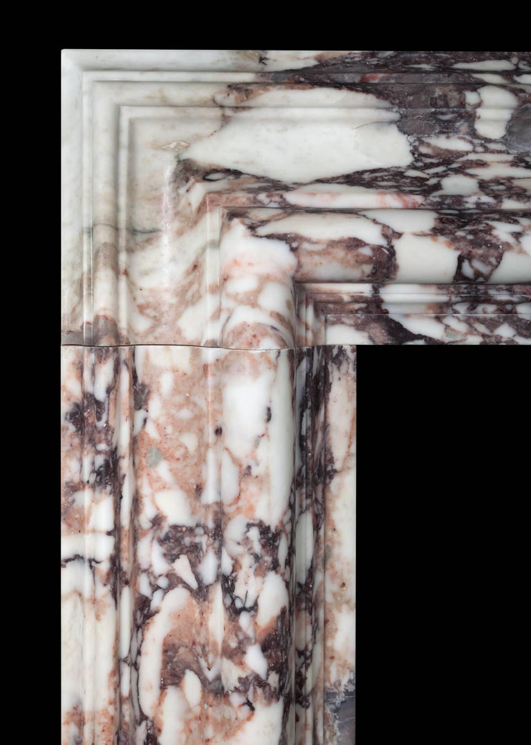 A large bolection fireplace surround of generous proportions. The substantial 12? (300mm) wide bolection molded frame, rests on plain square plinths. Carved from a block of beautifully figured, Breccia violetta marble, hand selected in Italy by