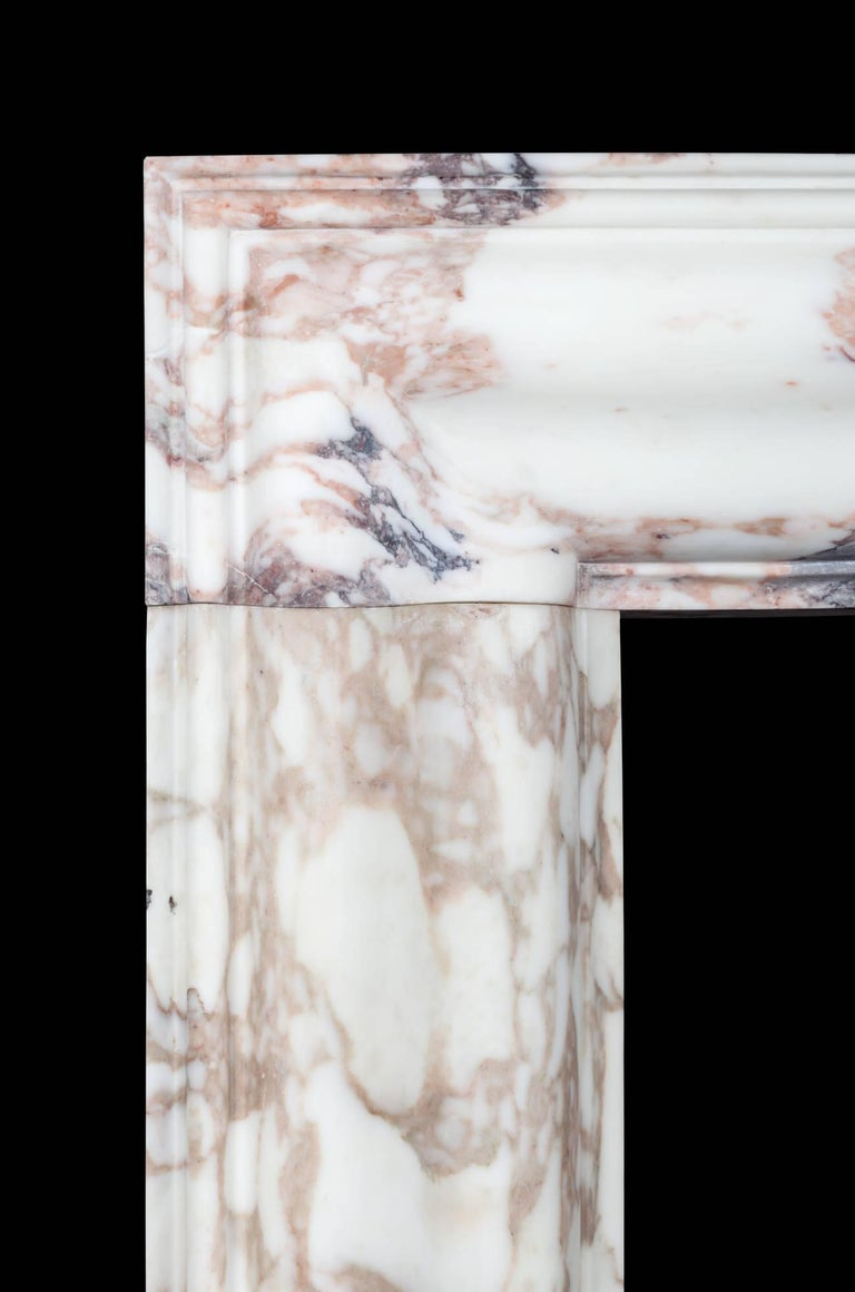 A Classic bolection fireplace with moulded frame on plain square plinths, carved from three solid pieces of marble with mason mitred corners. Made by Ryan & Smith from a beautiful block of Breccia marble sourced in Italy.   Medici Breccia This
