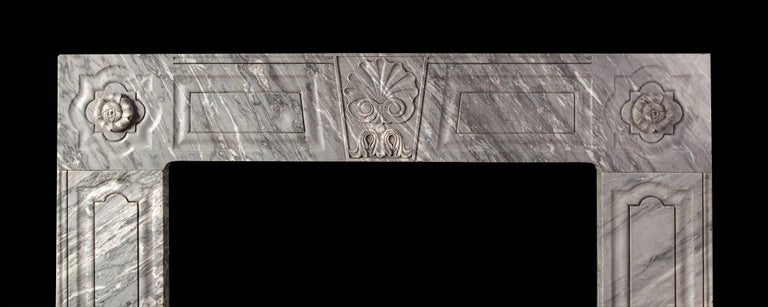 Carved from three pieces of Dove grey marble. The jambs and frieze having raised and fielded panels. The keystone carved with an oyster shell and the corners with stylized rosettes. This fireplace reflects the work of Irish stone cutter William