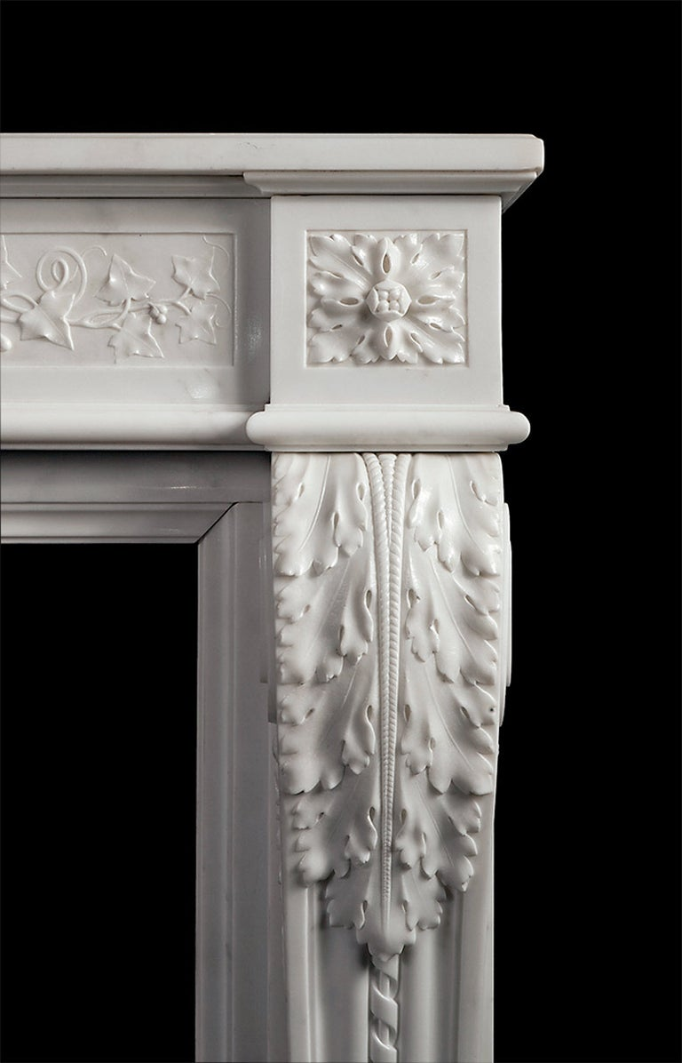 A finely carved white marble fireplace in the French Louis XVI style. The acanthus consoles taper and terminate with carved plinth mouldings. The running frieze carved with ivy vines and berries tied with ribbon in the centre.