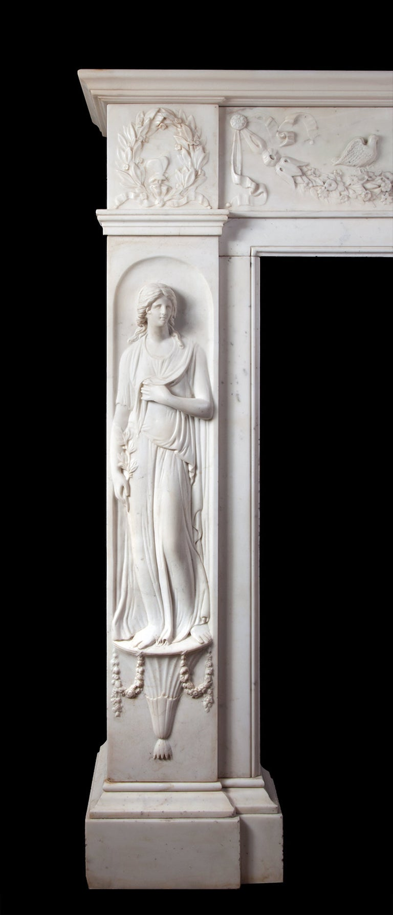 The rectangular moulded shelf sits above a frieze centred by an oval relief depicting Aphrodite and Cupid. To either side are swags of flowers with two dove birds resting. The jambs are of classical robed female figures, one with an olive branch and