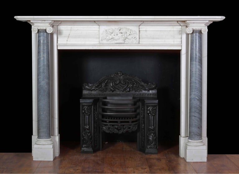 An attractive marble fireplace from the Regency period (1820s). Made from Italian white statuary and grey bardiglio marbles.  The jambs with tapering Ionic full rounded columns, supporting a rectangular moulded shelf. The centre plaque finely