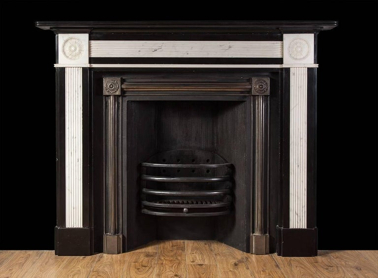 A very stylish and striking, black and white marble mantelpiece from the Regency period. The black Kilkenny marble jambs and frieze have inlaid white marble panels with reeded detail. The square corner blocks are finely carved with floral paterae,