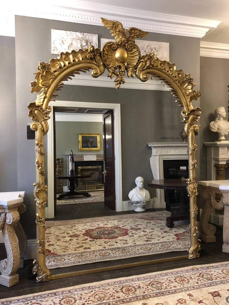 A carved giltwood mirror of very large-scale and great quality, made by Froom & Cribbs of London. The beautifully carved wooden frame decorated with flowers and foliage. The scrolled arched top centred by an open scallop cartouche with cresting