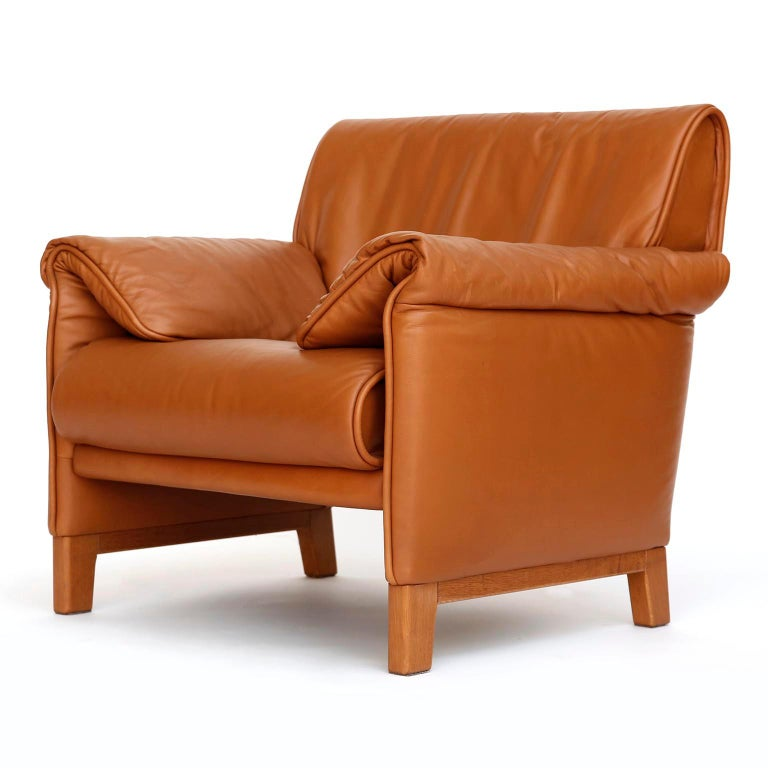 One of seven De Sede 'DS-14' armchairs in a warm high quality cognac brown leather with a solid Teak base, designed in 1989 and manufactured between 1989 and 1997. The chairs are in great and almost new condition. They are labeled inside with De