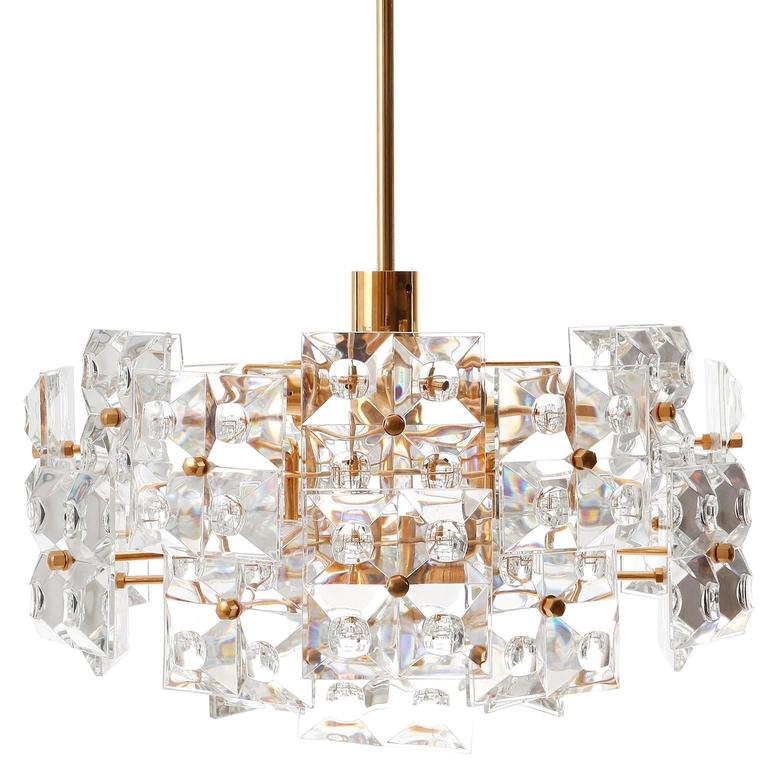 A very exclusive and high quality chandelier by Kinkeldey, Germany, manufactured in Mid-Century, circa 1970 (late 1960s or early 1970s). It is made of a gilded / gilt frame which holds large cut crystal glass with the dimensions of 4 x 4 in. (10 x