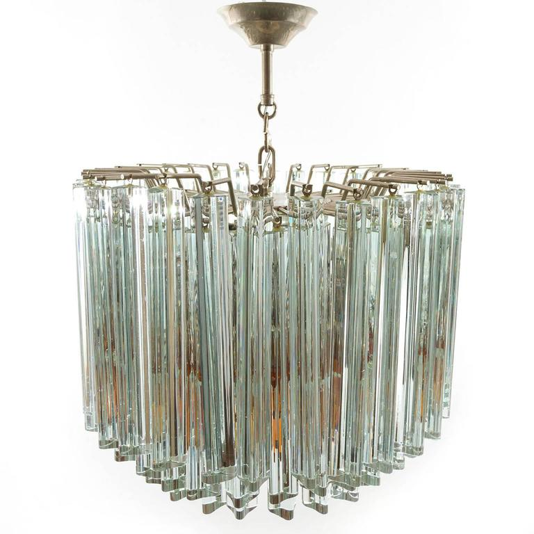 A wonderful Italian pendant light fixture or semi flush mount light by Venini, manufactured in midcentury, circa 1960. The light is made of a nice combination of clear, orange and amber/brown Triedri crystal glasses. One orange glass has been